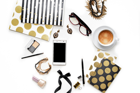 Flat lay fashion feminine home office workspace with phone, cup of coffee, stylish black gold notebooks, cosmetics and jewelry on white background. Womens business work desk form above with space for text