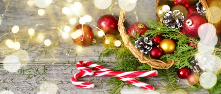 Long banner Christmas Basket with Gifts and Shining lights. Red balls, Pine cones, lollipop on Wooden Table Copy Space Drawing lights