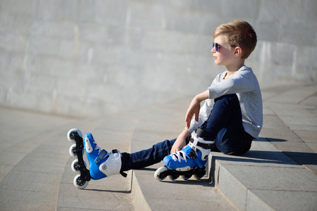 Boy siting with inline roller skates at outdoor skate park Banco de Imagens