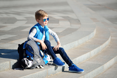 Young boy sitting near grey wall with inline roller skates and all protection at outdoor skate park