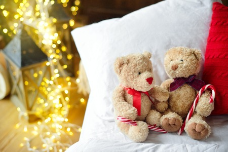 Two teddy bears siting on the bed with red candys near christmas tree. Stock Photo
