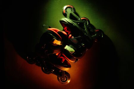 Close up view of roller skates inline skate or rollerblading on dark grunge background in neon blue yellow green light