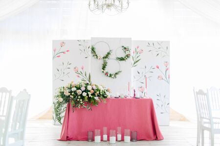 Wedding decor. Table for the newlyweds outdoor. Wedding reception. Elegant wedding table arrangement, floral decoration, restaurant.