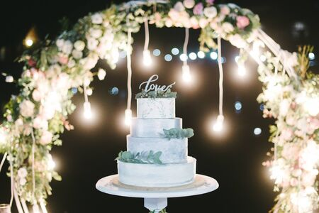 Decorated by flowers multilevel wedding cake with lights on the background 스톡 콘텐츠