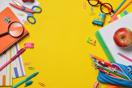 Colorful Back to School concept - office and student supplies on yellow background. Space for text. Flat lay
