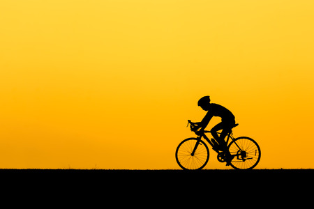 A silhouette of man cycling on the lawn in sunset. Stock Photo