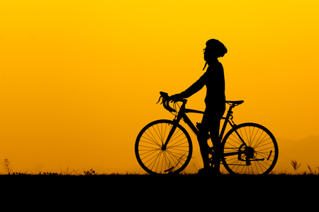 A silhouette of man wearing glasses standing with bicycle and him looking at the sky in sunset