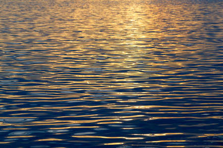 Sunset reflected in gentle waves at Sidney Spit, British Columbia, Canada