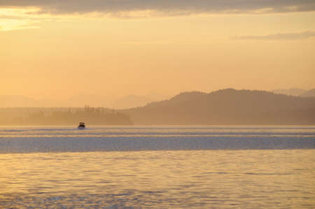 Motorboat heading into the sunset with yellowed layered islands in the background, British Columbia, Canada