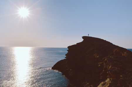 Epic landscape with man standing on the edge of the cliff. Sunset daytime with reflection on water. Sea and rocks mountains. Summer sport hiking experience. Unreal location with natural wow beauty.