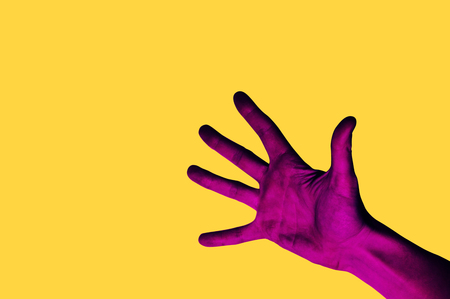 Isolated hand photo on yellow background. Pink hand collage style. Bright pop art template with space for text. Creative minimalistic backdrop.