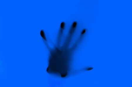 Hand in blue neon light behind transparent surface. Foggy blurred effect for different concept ideas. Trendy bold illumination. Abstract background