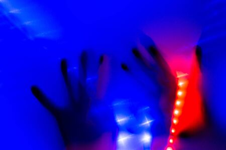 Hand in blue neon light behind transparent surface with red and purple led light stripes. Foggy blurred effect for different concept ideas. Trendy bold illumination.
