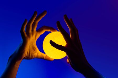 Man holding yellow moon shape illuminated sphere