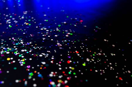 Colorful lights blurred glitter background. Abstract illuminated texture. Christmas, new year or birthday celebration. Night life photography. Blue and purple neon colors overlay. Space for text.