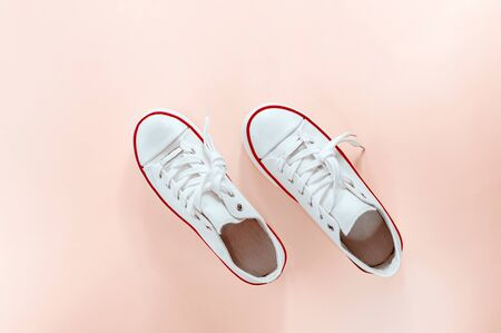 White trendy white sneakers on creamy peach background. Flat lay, top view. Place for text. Minimalistic style composition. Sports wear, active lifestyle concept.
