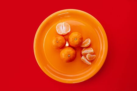Tangerines on orange plate. Monochrome styled flat lay on bold red background. Fresh citrus fruits.