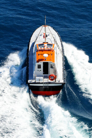 powerfully: A pilot boat powerfully navigates in a blue sea, leaving a big white foam behind it