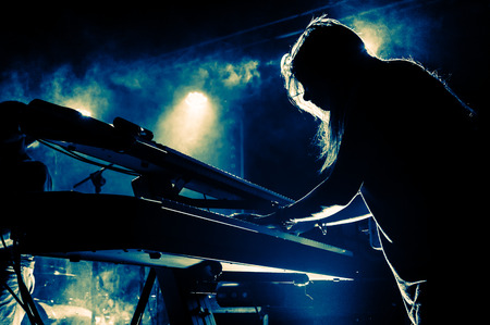 keyboard instrument: Female keyboards player on stage during concert, backlight, colors intentionally altered Stock Photo