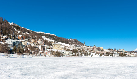 Stunning snowy view of Saint Moritz Swiss town, with icy lake in the foreground