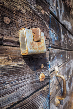 oxidize: Rusty padlock on wooden door, vertical frame