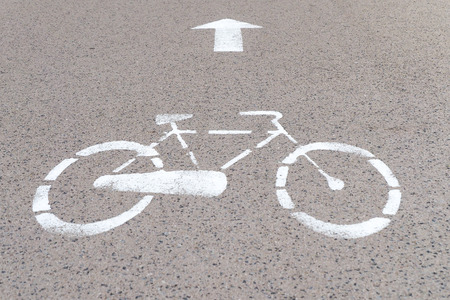 one lane road sign: Road mark on asphalt Indicating reserved bike path, gray background, bicycle silhouette and straight arrow