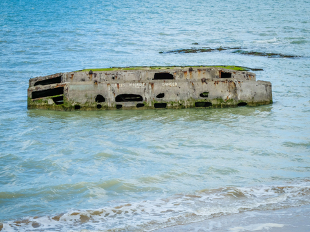 seaa: Ruins of artificial Mulberry harbor built by the Allies in Arromanches, Normandy, France before the Debarquement of the D-Day in 1944.