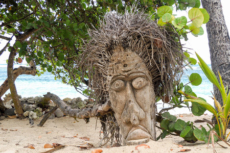 ceremonial: A voodoo mask graven in a tree trunk on a tropical beach with sea in the background