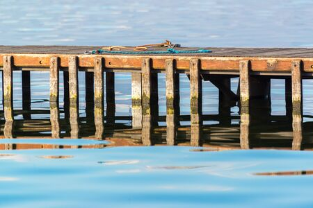 chords: Section of a wooden pier emerging from calm water, with some chords on it, symmetric reflections Stock Photo