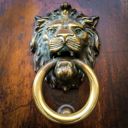 doorknocker: Traditional door knocker on a wooden door, brass made, showing the face of a lion. Typical ornament for old italian houses. Stock Photo
