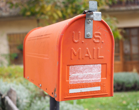 united states postal service: An old home letter box, orange painted, with background of rural house Stock Photo