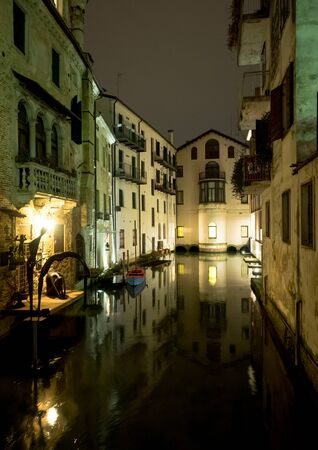 italian architecture: Night view of Treviso canal with surrounding buildings, typical italian architecture, vertical frame Stock Photo