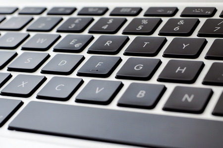 iluminado a contraluz: Vista de cerca de un teclado de portátil moderna, teclas negras y cuerpo de aleación de plata Foto de archivo