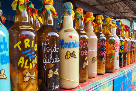 Traditional flavoured rhum bottles on the desk of a market stall in Sainte Anne, Guadeloupe