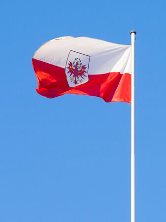 waft: Flag of Tyrol waving with background of pleasant blue sky. Vertical image.