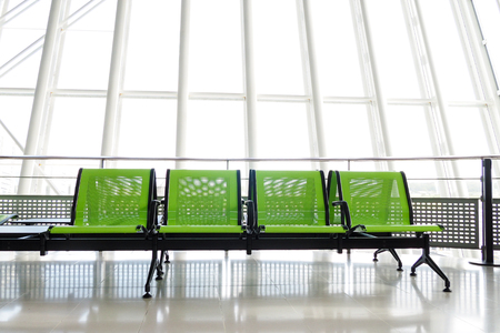 Bench with green seats in the departure hall of an airport, with giant windows in the background. Stock Photo