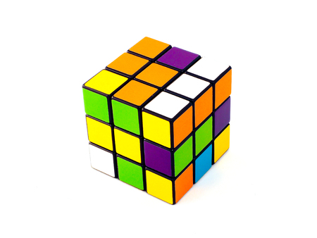 unsolved: Rubiks cube with unusual colors on white background. It was invented by Hungarian architect Erno Rubik in 1974.