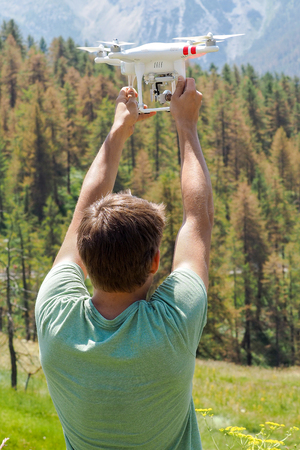 Young man holding a white drone ready to fly over mountain forest, vertical image