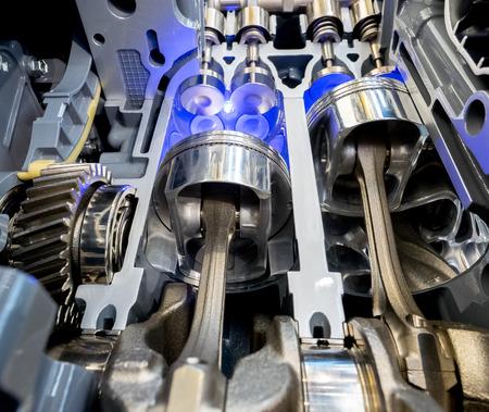 Binnen mening van motor, sluit omhoog detail van twee zuigers in cilinder met vier kleppen, sommige toestellen opzij.