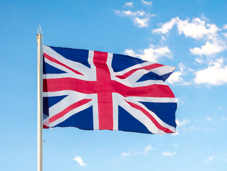 Union Jack, traditional United Kingdom flag, waving in blue sky, copyright space Stock Photo