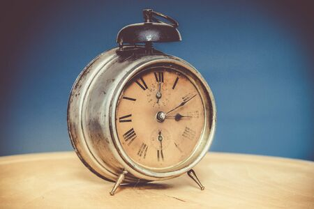 Vintage alarm clock on wooden table, blue background, deliberately grainy Stock Photo