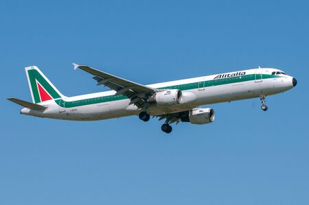 London, UK, April 9 2011: 2-engines Airbus A321 of Alitalia italian national carrier landing at Heathrow airport.