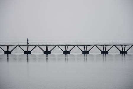 Lonely man walking on a bridge over water in Lisbon, foggy atmosphere, copyspace