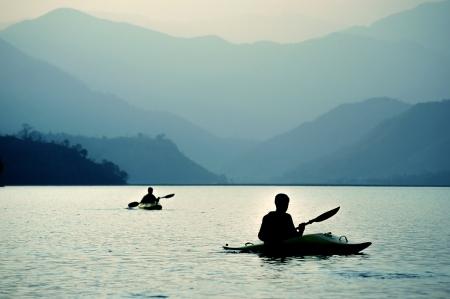 canoa: Kayak en la puesta de sol en las montañas Foto de archivo