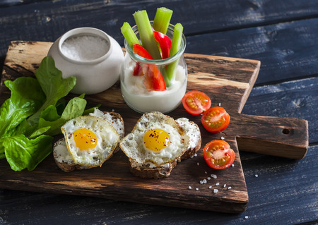 Sandwiches with cheese and fried quail eggs, fresh herbs and cherry tomatoes, Greek yogurt, celery and pepper. Healthy breakfast or snack. On a wooden rustic board Archivio Fotografico