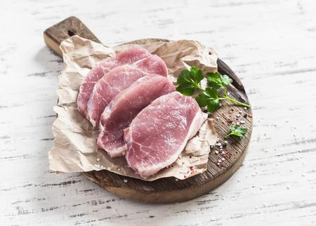 Raw pork chops  on a rustic wooden cutting board