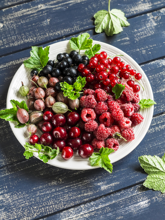 black currants: Assortment of berries - raspberries, gooseberries, red currants, cherries, black currants on a white plate on a wooden background. Healthy food, delicious summer dessert