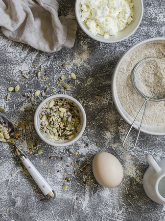 multi grain: Ingredients for cooking whole grain multi seed bread - whole wheat flour, eggs, ricotta cheese, seeds, on a grey stone background. Baking background Stock Photo