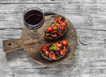Tomatoes and olives bruschetta and a glass of red wine on rustic wooden background