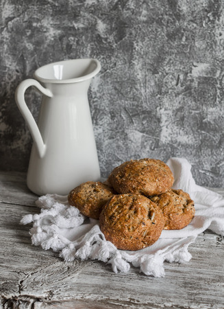 multi grain: Multi seed whole grain rolls and a enamel jug on a grey wooden rustic background
